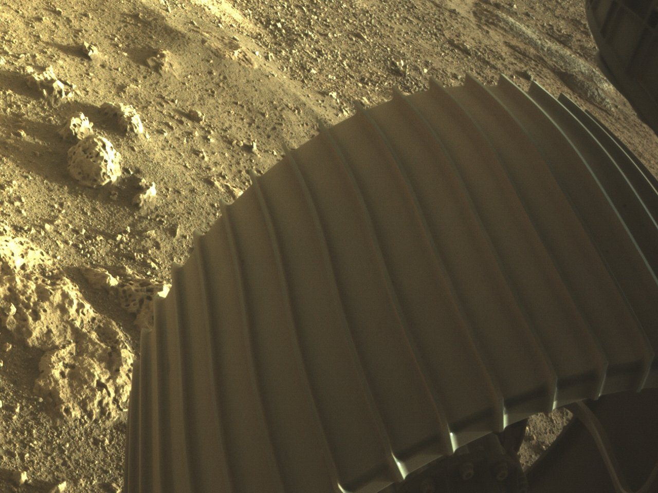 Photo of the Mars rover Perseverance's wheel and rocks at first glance.
