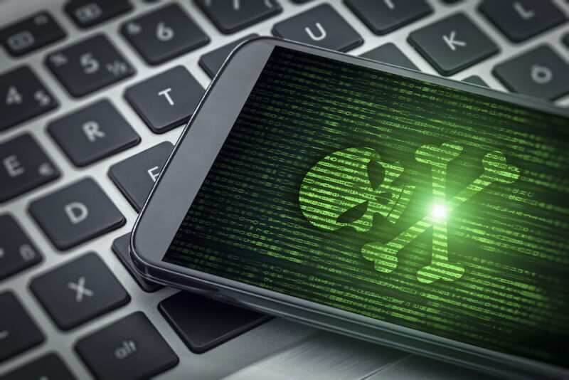 Stock photo of skull and crossbones on a smartphone screen.