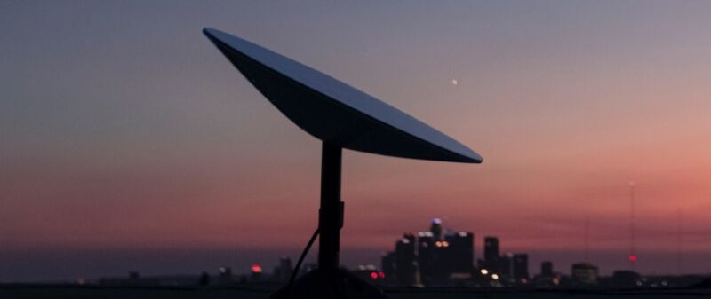 A SpaceX Starlink user terminal, also known as a satellite dish, seen against a city's skyline.