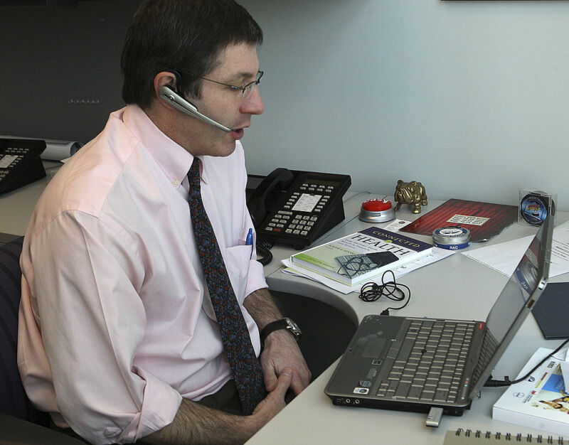A man with his sleeves rolled up speaks into a headset while staring at a laptop.