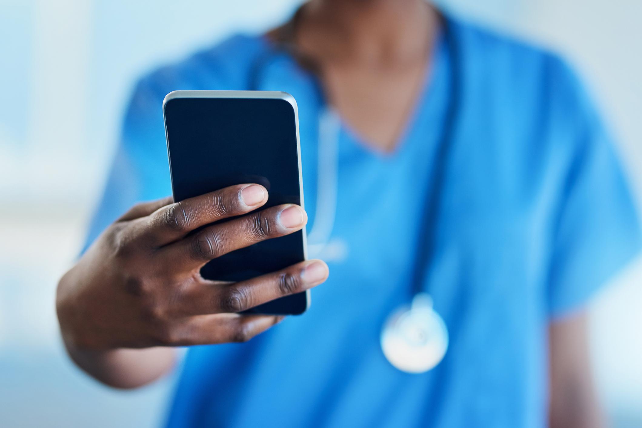 Closeup shot of an unrecognizable nurse using a cellphone in a hospital