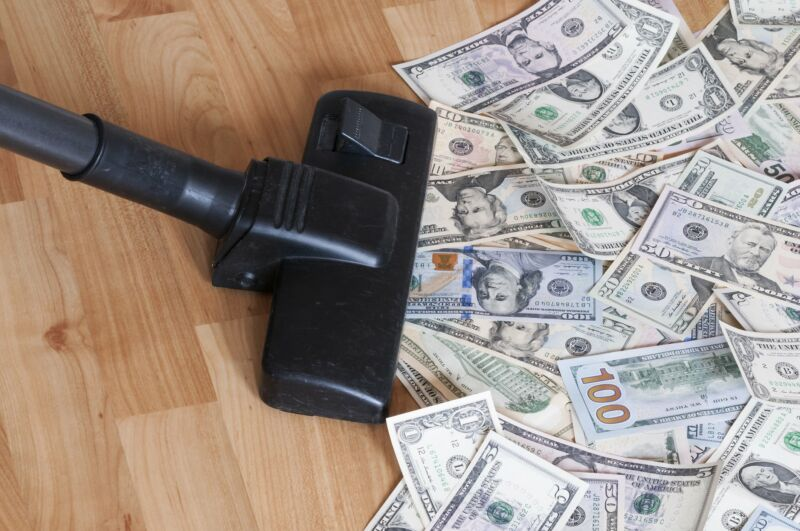 Vacuum cleaner sucking up a pile of money.